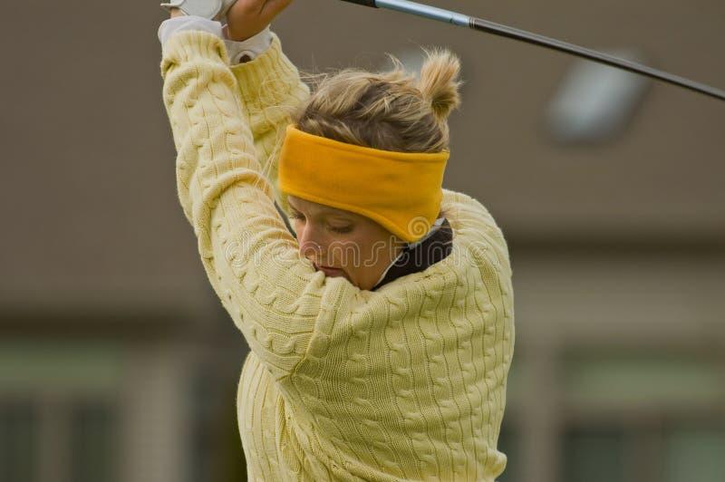 Female collegiate golfer swinging golf club stock images