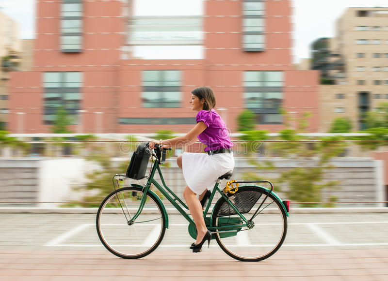 Female commuter cycling. Mixed-race businesswoman going to work by bike