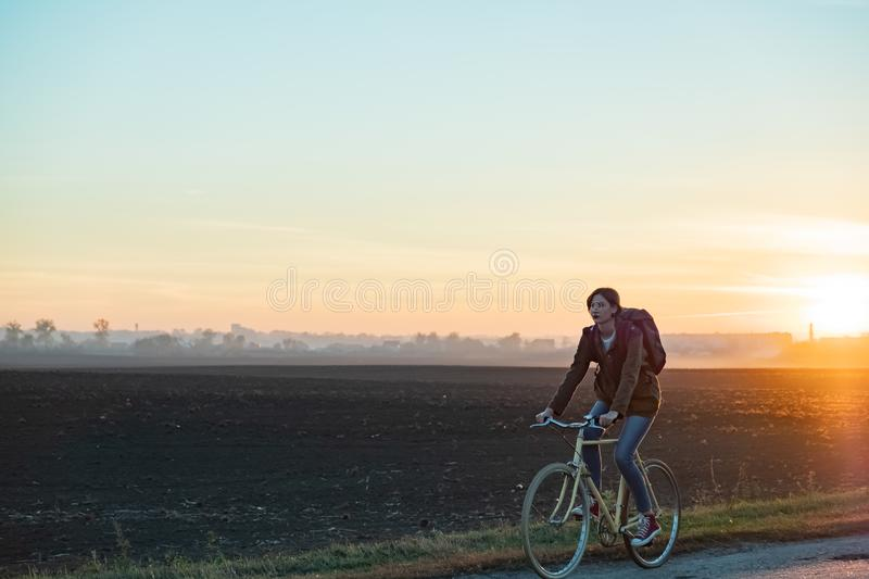 Female commuter riding a bike out of town in rural area. Young w stock photo