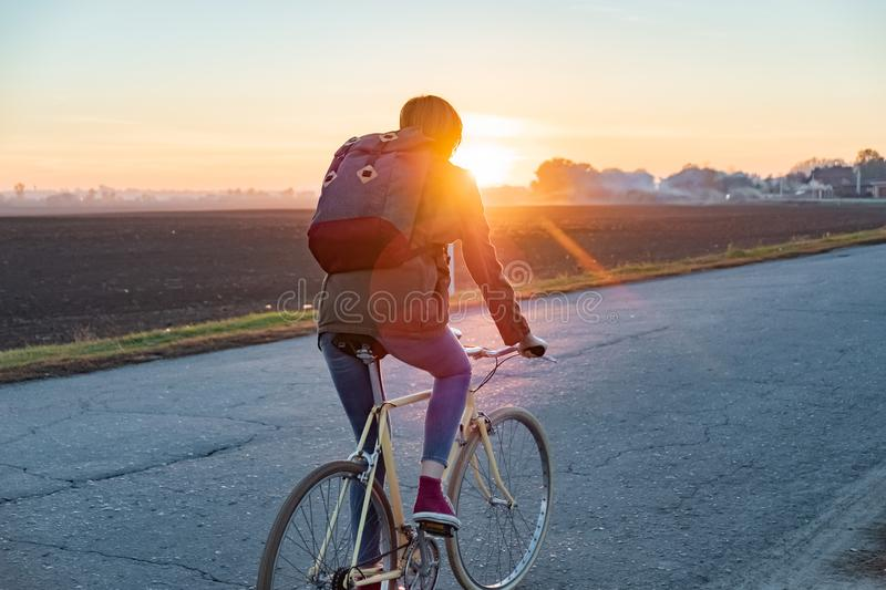 Female commuter riding a bike out of town to a suburban area. Woman cycling along the road at sunset royalty free stock image