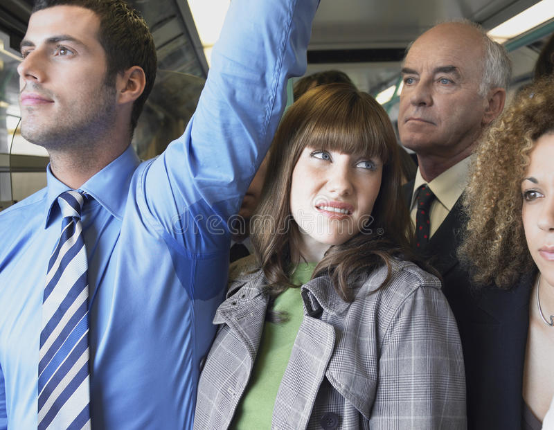 Female Commuter Standing by Man's Wet Armpit In Train. Closeup of a female commuter standing by man's wet armpit in a crowded train stock photos