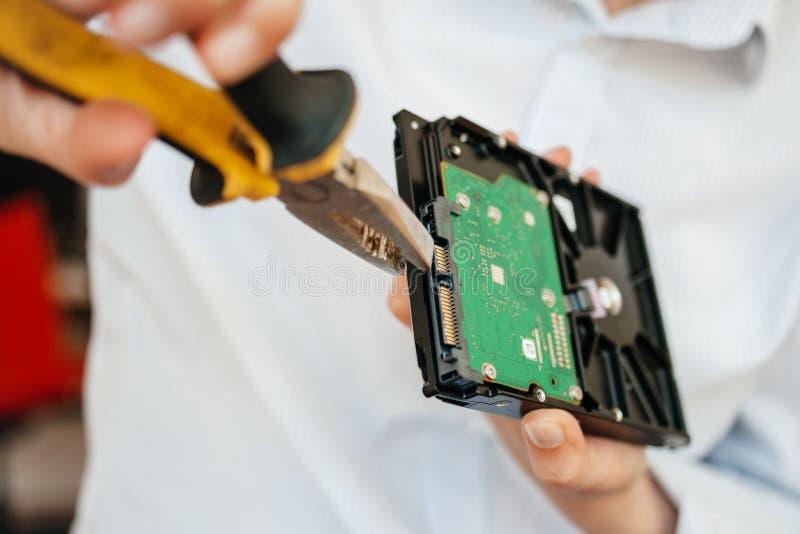 Female IT computer repair IT woman using yellow metal pliers royalty free stock photo