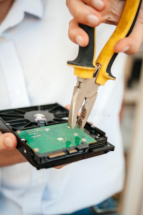 Female IT computer repair IT woman using yellow metal pliers royalty free stock photography
