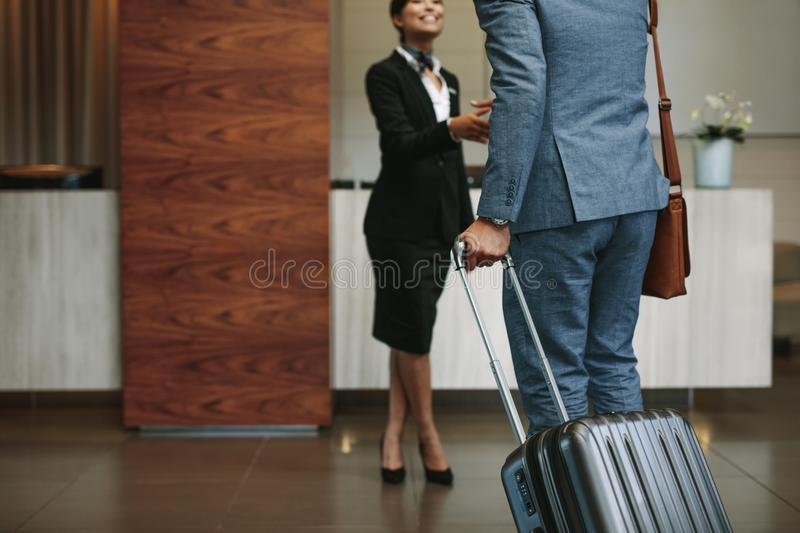 Concierge welcoming guest at hotel lobby. Female concierge welcoming business men at hotel lobby. Receptionist greeting guest at hotel hallway stock photography