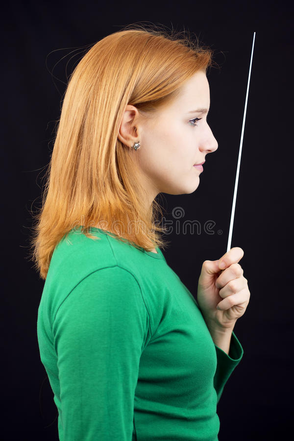 Female conductor. Portrait of female conductor in green stock photo