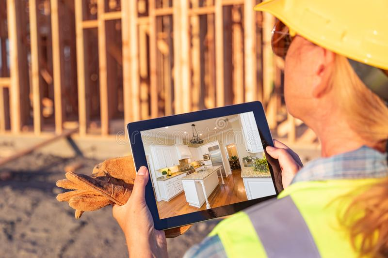 Female Construction Worker Reviewing Kitchen on Computer Pad stock photos