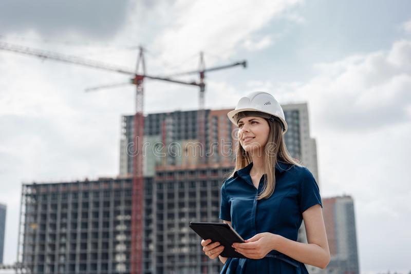 Female construction engineer. Architect with a tablet computer at a construction site. Young Woman looking, building stock images
