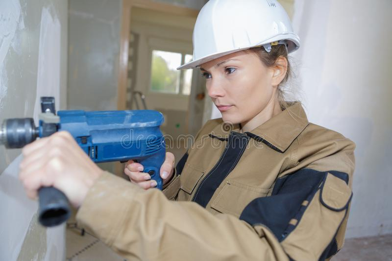 Female construction worker demolishing old brick wall with drill. Female stock photos