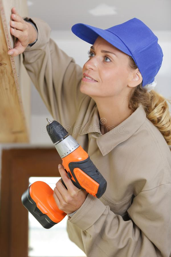 Female construction worker drilling. A female construction worker drilling stock photo
