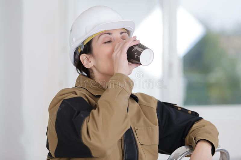 Female construction worker having coffee breake royalty free stock image