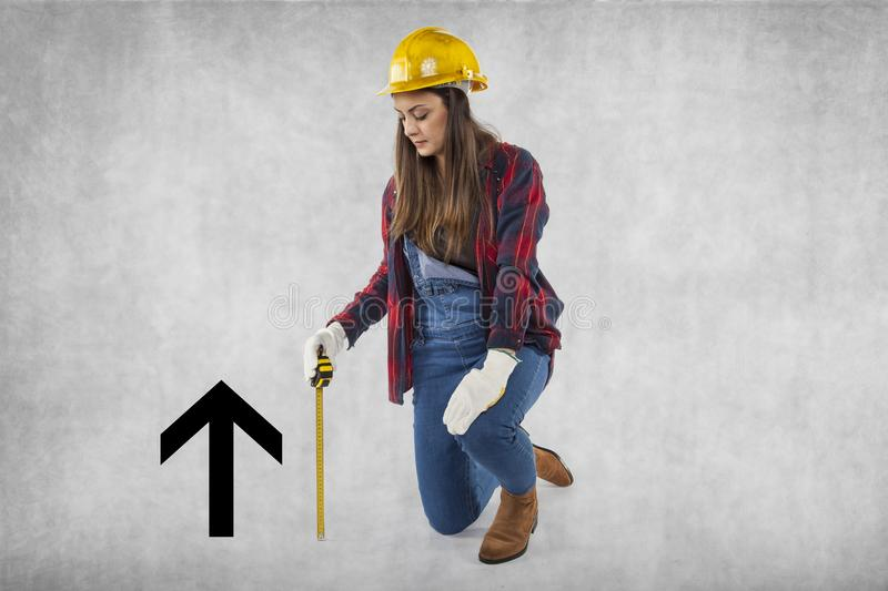 Female construction worker kneeling next to the arrow royalty free stock photo