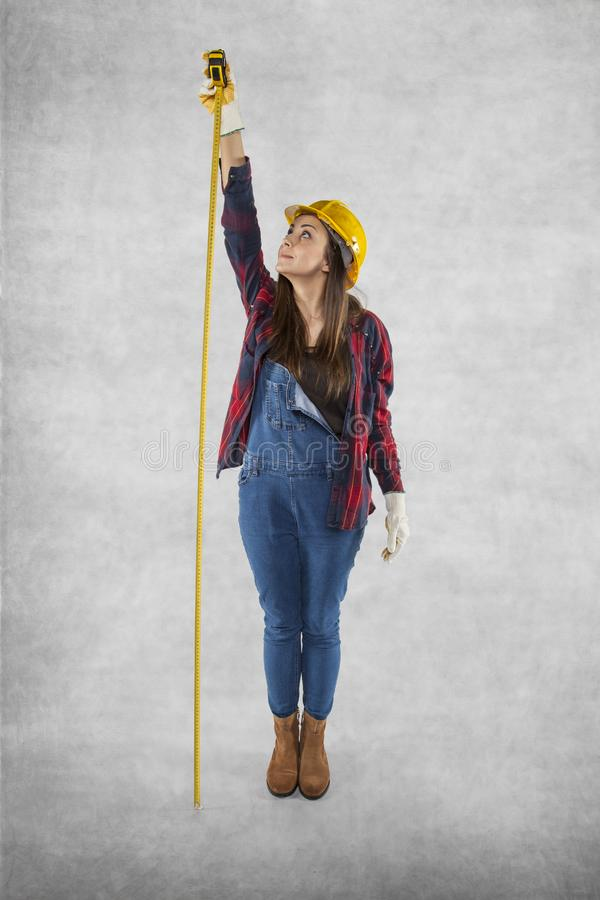 Female construction worker measures very high royalty free stock images
