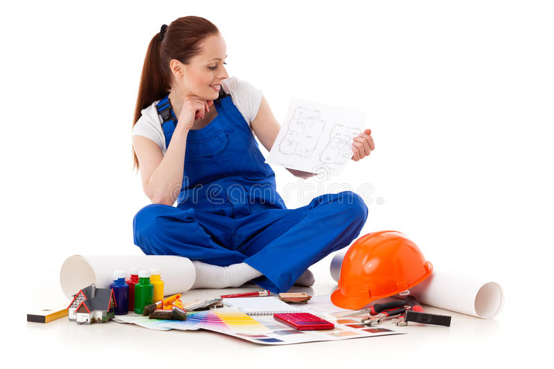Female construction worker with plan of house. royalty free stock photo