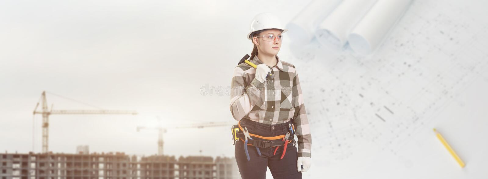 A female construction worker in safety helmet holds a hammer. Against city background stock photos