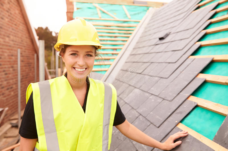 Female Construction Worker On Site Laying Slate Tiles stock photos