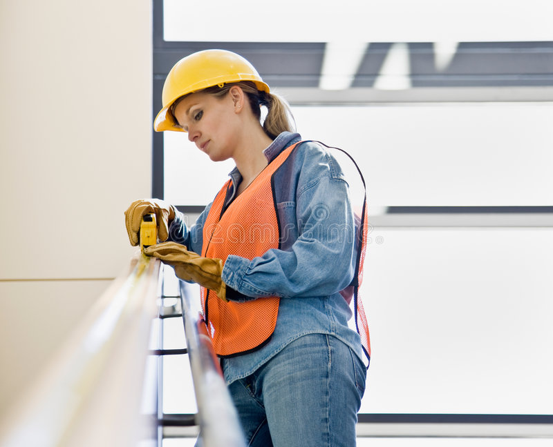 Female construction worker taking measurement. Female construction worker carefully taking measurement with measuring tape stock photo