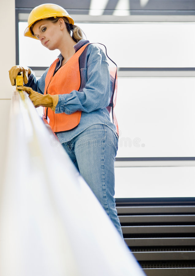 Female construction worker taking measurement. Female construction worker carefully taking measurement with measuring tape stock photos