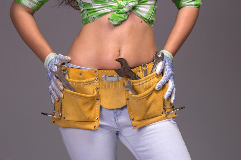 Female Construction Worker With Tool belt. Close up view royalty free stock image