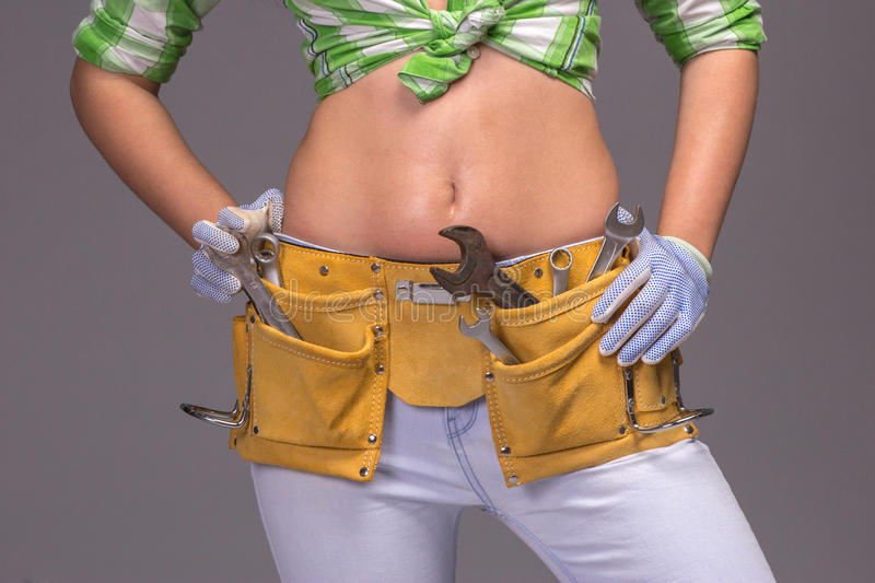 Female Construction Worker With Tool belt. Close up view royalty free stock photography