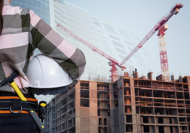 A female construction worker with white helmet against city background royalty free stock images