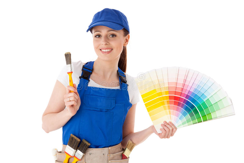 Female construction worker. Young woman in coverall with a color guide and paintbrushes on a white background royalty free stock photography