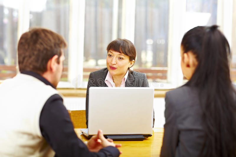 Female consultant advising couple. Sitting at the computer stock image