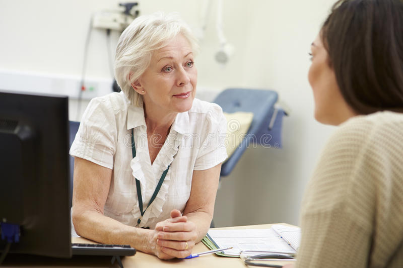 Female Consultant Meeting With Teenage Patient stock photography