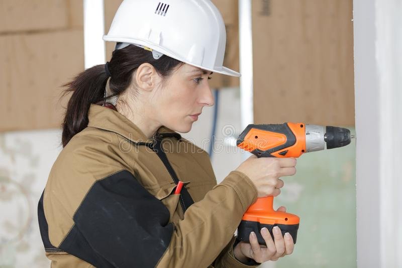 Female contractor drilling into wall stock photo