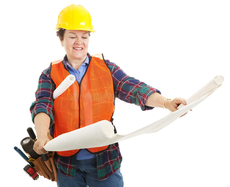 Female Contractor Examines Blueprint stock images