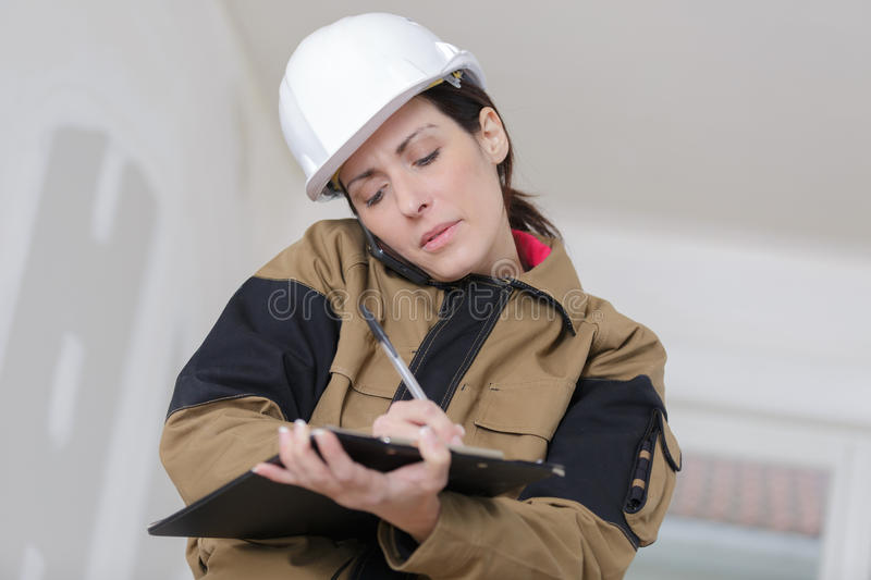 Female contractor holding clipboard and talking on phone stock images