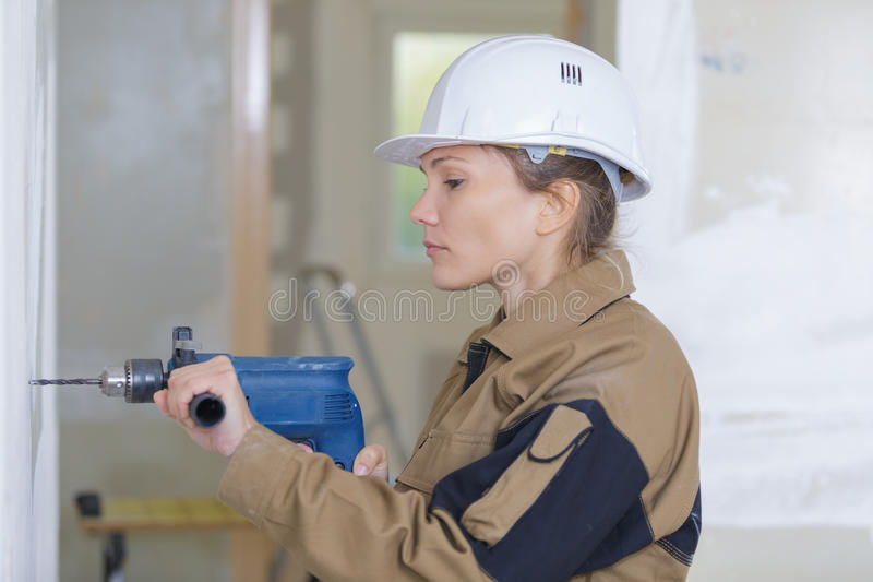 Female contractor holding driller stock photography
