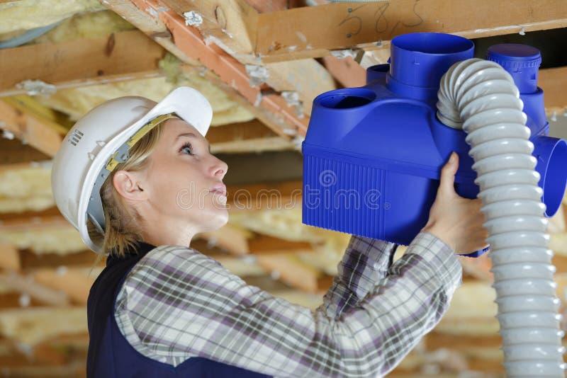 Female contractor installing plastic ventilation hub stock photography