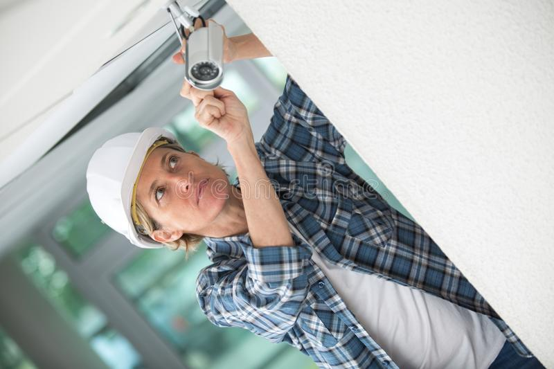 Female contractor installing surveillance camera royalty free stock photo