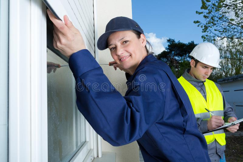 Female contractor installing window shutter royalty free stock photography
