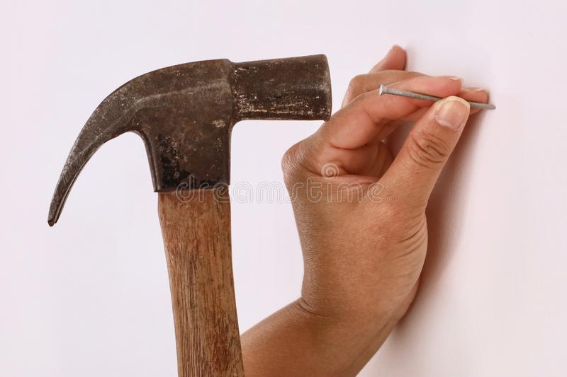 A female contractor using a hammer to hammer in a nail royalty free stock image