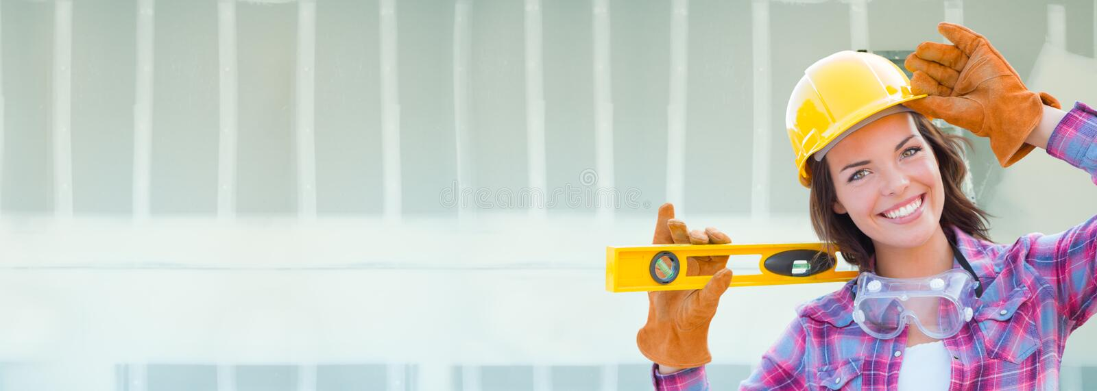 Female Contractor Wearing Hard Hat Against Drywall Banner Background with Ladder royalty free stock images