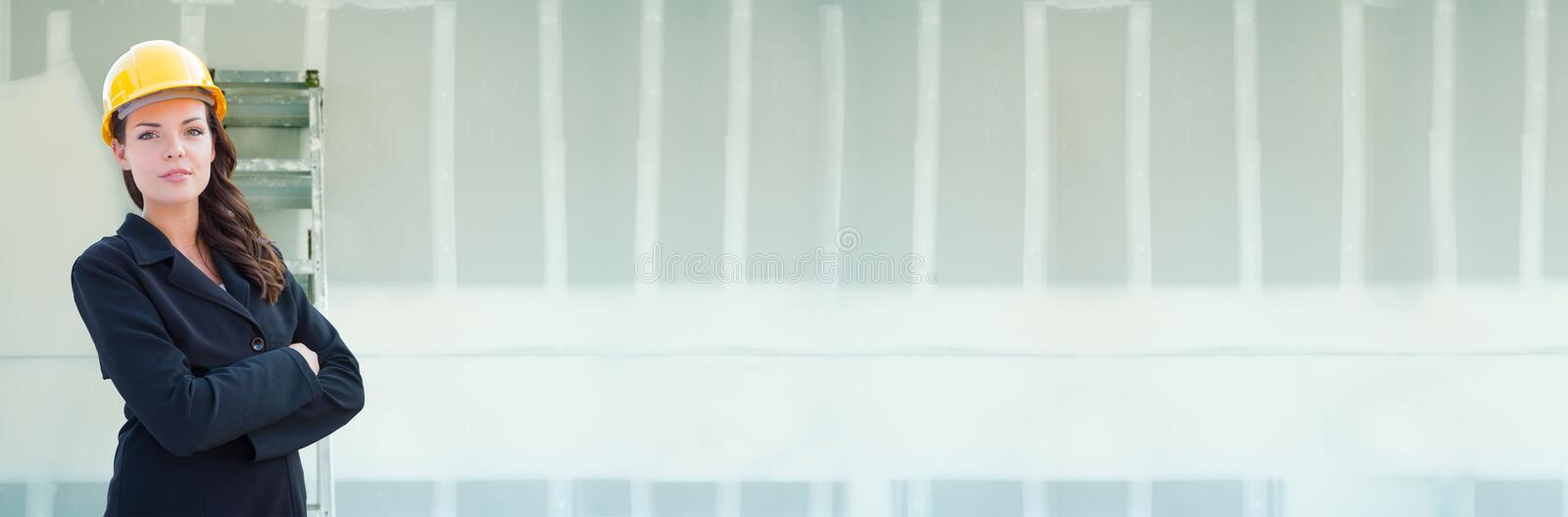 Female Contractor Wearing Hard Hat Against Drywall Banner Background with Ladder royalty free stock photography
