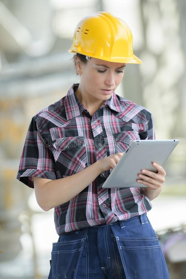 Female contractor at work site using ipadtablet. Female contractor at a work site using an ipadtablet royalty free stock image