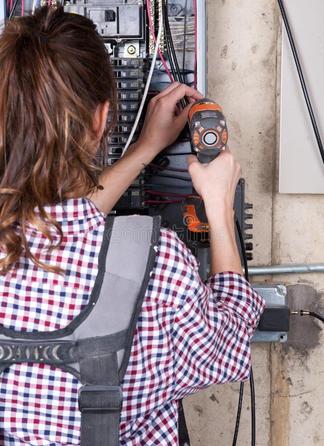 Female contractor worker holds cordless drill gun royalty free stock image