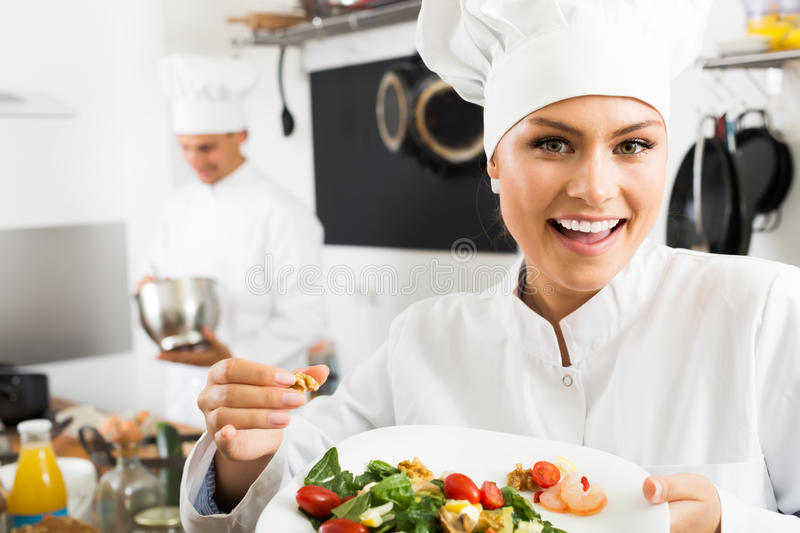 Female cook holding plate with green salad stock photo