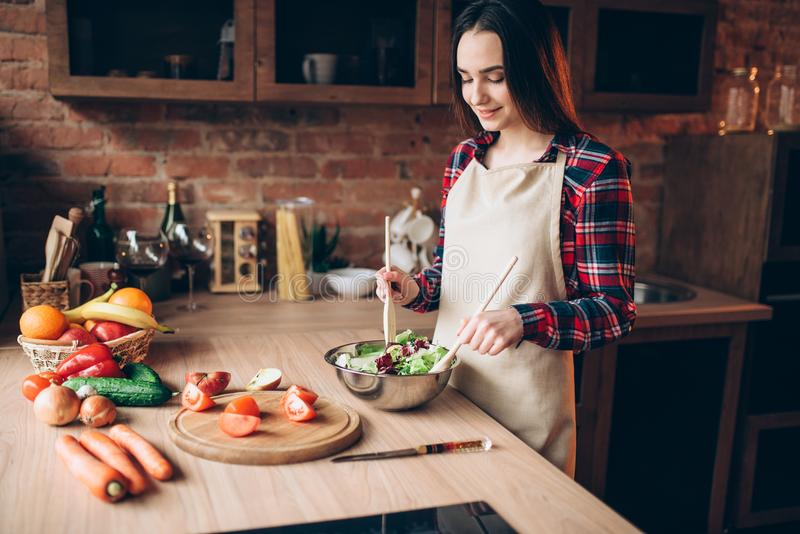 Female cook, salad cooking on the kitchen stock photography