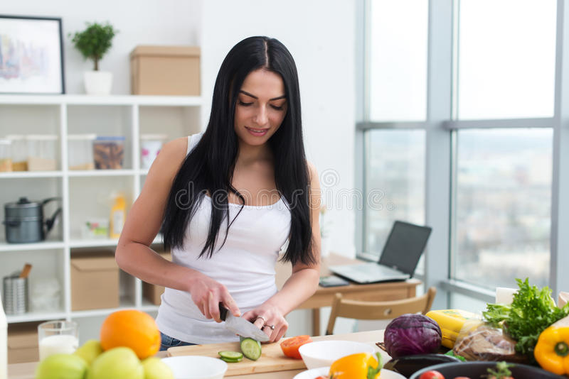 Female cook slicing green cucumber, cooking fresh vegetable salad on cutting board at her kitchen worktop. royalty free stock photos