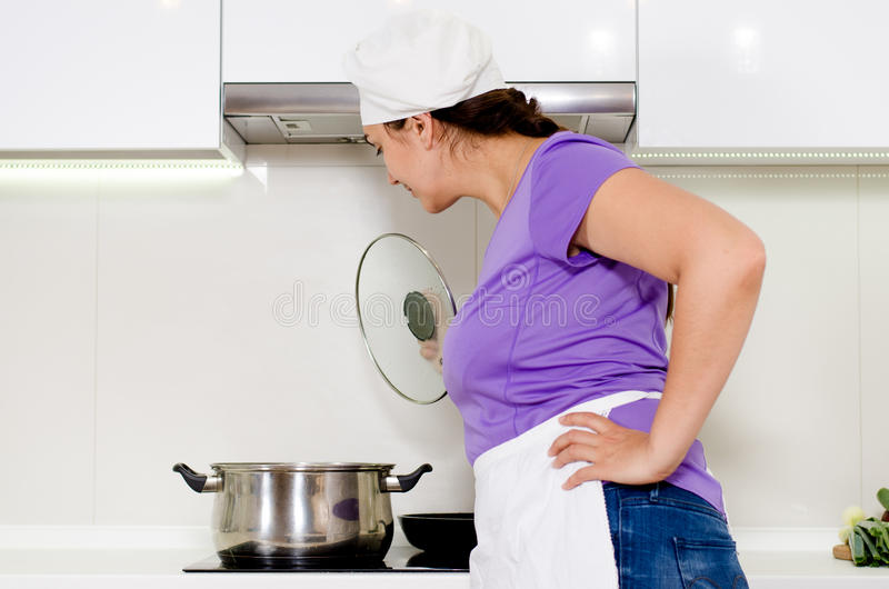 Female cook watching a pot boil. On the stove in her white apron and chefs toque stock photography