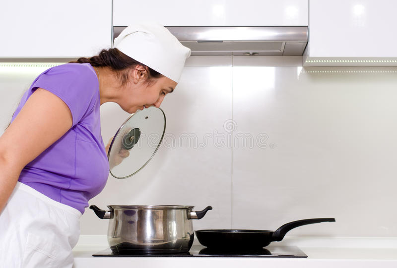 Female cook watching a pot boil. On the stove in her white apron and chefs toque stock photos
