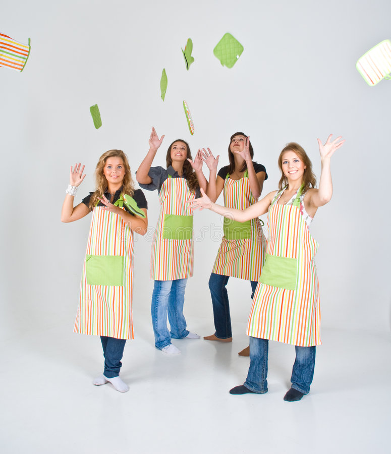 Female Cooks in Aprons. Four girls in aprons throwing up pot holders stock photo