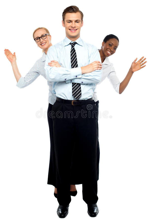 Female Corporate Waving Hi While Man Stands Tall Stock Photography