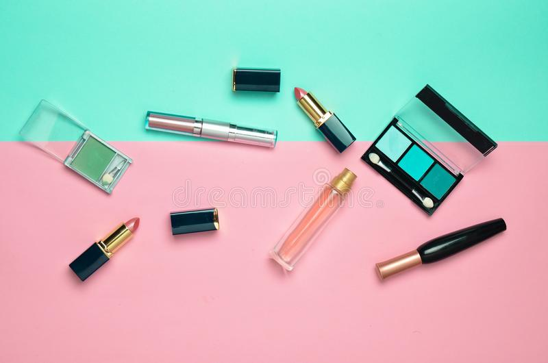Female cosmetics for make-up layout on a pastel background. Cosmetic shadows, make-up brush, eyeshadow lipstick, perfume bottle. stock photography