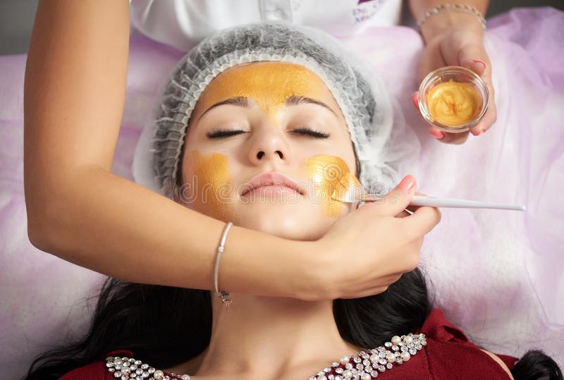 Female cosmetologist is applying gold mask with a soft brush to a brunette client of a beauty salon. Female cosmetologist is applying gold mask with a soft brush stock image