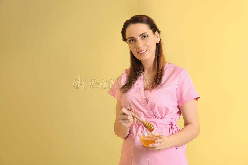 Female cosmetologist holding dipper and bowl with honey on color background stock image