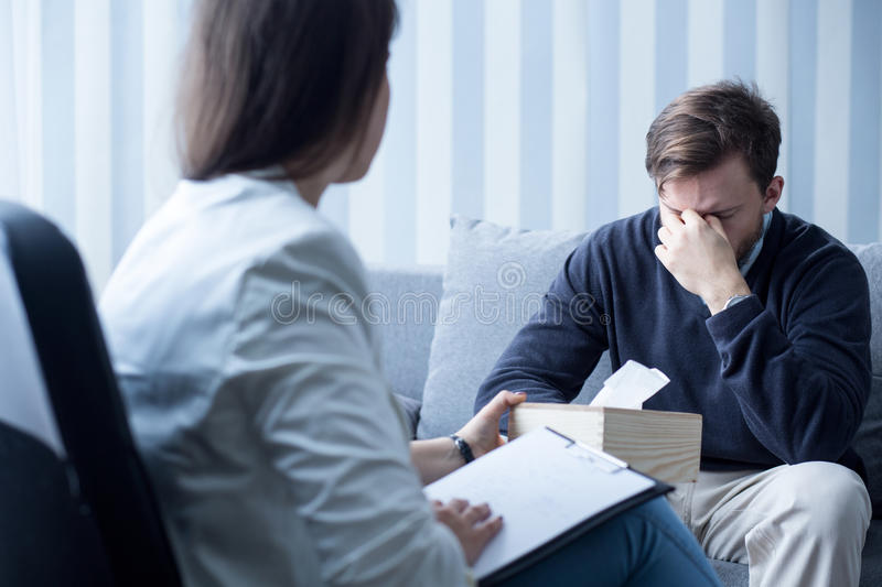 Female counselor helping despressed man. Photo of professional female counselor helping depressed man royalty free stock photography